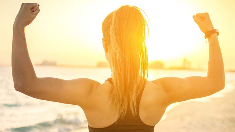 back facing shot of a young blonde woman with long hair standing in the sunset on a beach holding a strong pose with her fists up flexing her biceps. She is silhouetted against a city backdrop as the waves roll in to the front of her